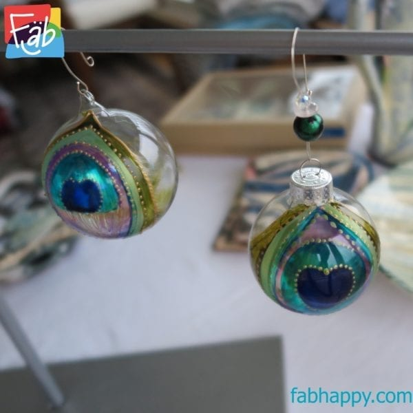 both Peacock Feather Baubles hanging on a stand